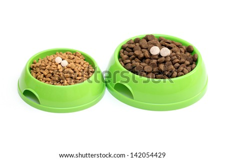 dog dishes with food garnished with vitamins isolated on white