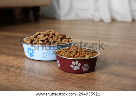 Dog food in bowls on floor at home - stock photo