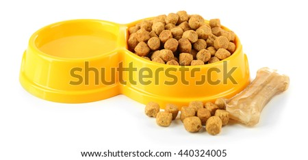 Dog food in yellow plastic bowl on white background - stock photo