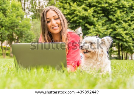Dog is watching it's owner using pc. Young attractive girl is studying lying in the park with her dog. Concept about dog, people, nature and technology - stock photo