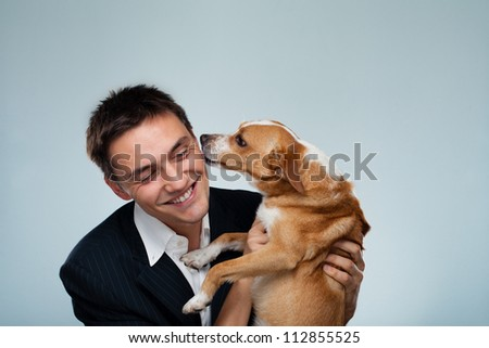 Dog kissing his owner - Young business man have fun with his dog - stock photo