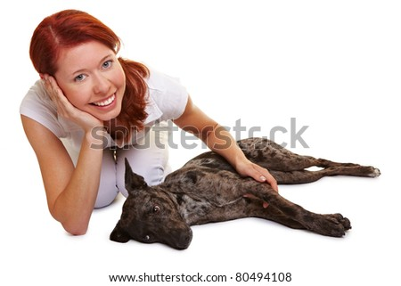 Dog laying beside smiling happy redhaired woman