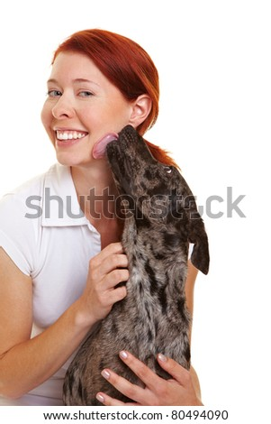 Dog licking over cheek of a happy woman - stock photo