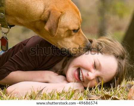 Dog making girl laugh on grass - stock photo