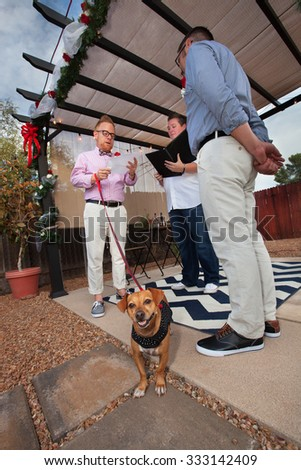 Dog on leash in marriage of gay men outdoors - stock photo