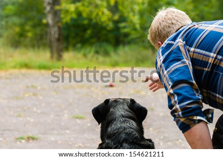Dog owner trains his labrador retriever on outdoor, horizon format - stock photo