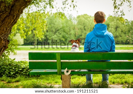 dog sitting on a bank with owner and enjoying the view - stock photo