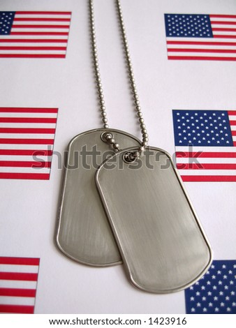 Dog tags and the flag of America. Focused on the dog tags. - stock photo