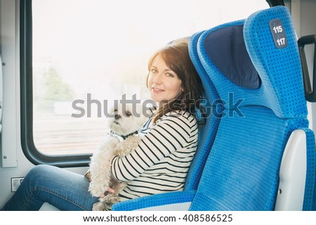 Dog traveling by train with his owner - stock photo