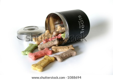 """Dog treats spill from a canister labeled """"good treats"""". - stock photo"""