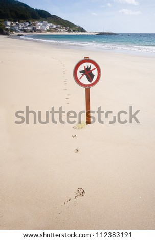 Dogs forbidden sign next to a line of dog paw prints.  The dog has urinated on the base of the sign.  Lovely beach and blue sea and sky in the background. - stock photo