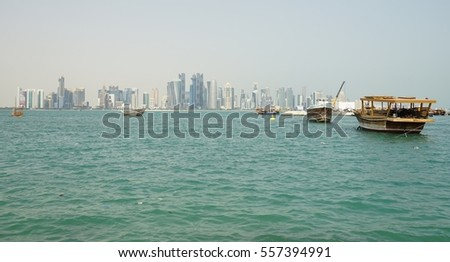 DOHA, QATAR -22 DEC 2016- Day view of the modern Doha skyline with a traditional Dhow wooden boat in front. The capital of Qatar includes many supertall highrise skyscrapers.