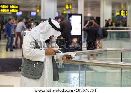 DOHA, QATAR - FEBRUARY 18, 2014: Muslim man wearing traditional clothes holding Kuran and looking at cell phone at Doha International Airport, the only commercial airport in Qatar. - stock photo