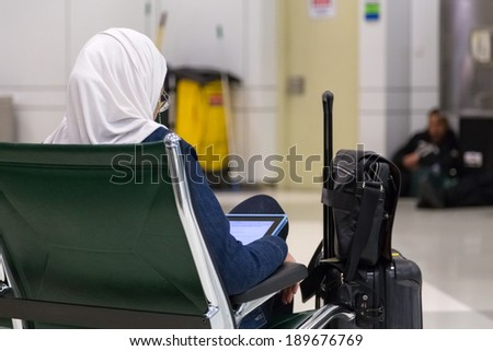 DOHA, QATAR - FEBRUARY 18, 2014: Muslim woman wearing traditional clothes sitting and looking at tablet at Doha International Airport, the only commercial airport in Qatar. - stock photo