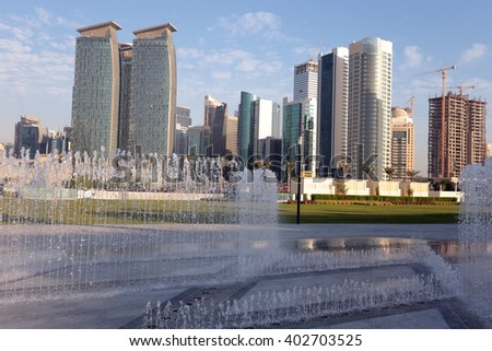 DOHA, QATAR - FEBRUARY 17, 2016: Skyscrapers in Doha business district seen behind newly installed fountains in Hotel Park, Dafna.