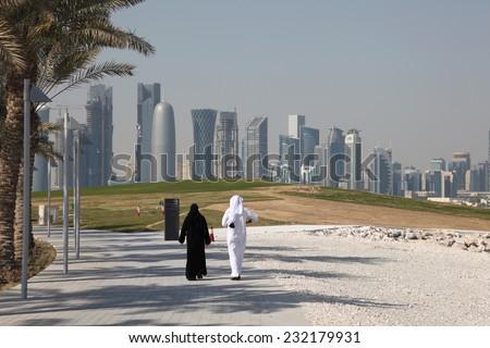 DOHA, QATAR - JAN 8: Arabic couple walking in front of the Doha downtown skyline. January 8, 2012 in Doha, Qatar, Middle East - stock photo