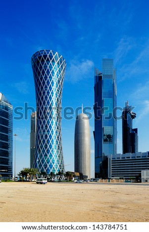 "DOHA, QATAR - JUN 17: 200 m tall ""Tornado Tower"" of the West Bay on Jun 17, 2013 in Doha. The hyperbolic shape of the tower is intended to represent a desert whirlwind, hence the name ""Tornado Tower"""