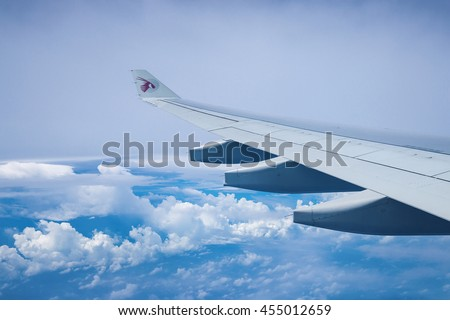 DOHA, QATAR - JUNE 9, 2016: A view of the airplane wing as seen through window of an aircraft Qatar Airways. Qatar Airways is included in the list of seven airlines with the highest five-star rating