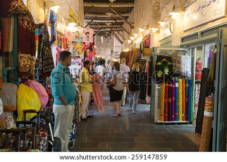 DOHA, QATAR - MARCH 8, 2015: Shopkeepers and shoppers in the textile section of the Souq Waqif arcade, a major tourist attraction, - stock photo