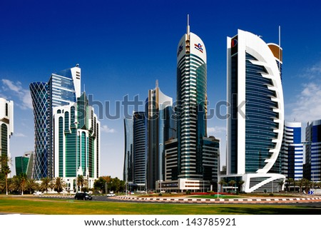 DOHA, QATAR - MAY 2: Tall buildings of the West Bay on May 2, 2013 in Doha, Qatar. The West Bay is rapidly expanding urban center of Doha with numerous skyscrapers gracing the skyline of the city - stock photo