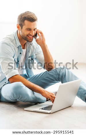 Doing business at home. Smiling young man working on laptop and talking on the mobile phone while sitting on the floor at his apartment - stock photo