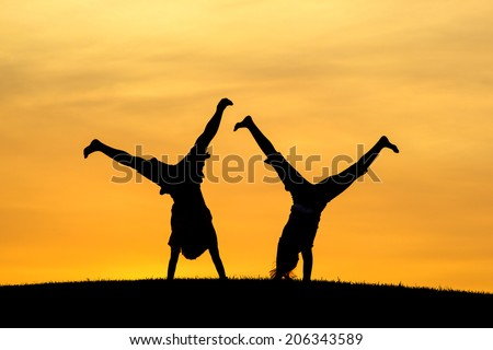 Doing cartwheels together.  - stock photo