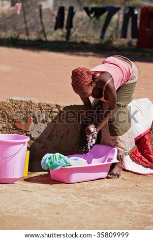 doing laundry, young African woman in the yard washing  manually the dirty  clothes - stock photo