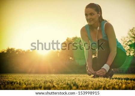 Doing Sport in the sunset / Young woman preparing to run in a playground, sunset in the background - stock photo