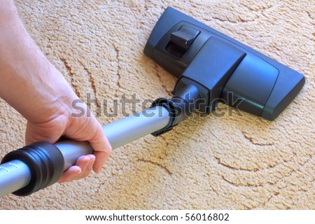 Doing the housework with the vacuum cleaner - stock photo