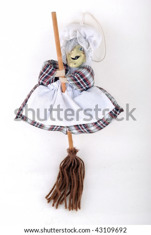 Doll a witch with a broom on a white background - stock photo