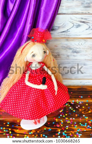 Doll-artist in a red dress in a white polka-dot with a microphone on stage