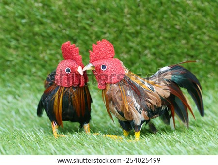 Doll chicken  on a background of green grass. - stock photo