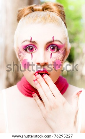 Doll Face Is A Woman With Big Eyes, Wearing Artistic Makeup, Cheek Buttons, Hair In Bun, Neck Scarf And Gesturing A Shocked Horrified And Awestruck Expression - stock photo