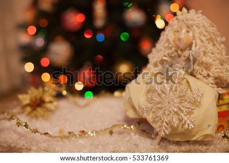 doll fairy princess sitting under the Christmas tree with snowflake in hands