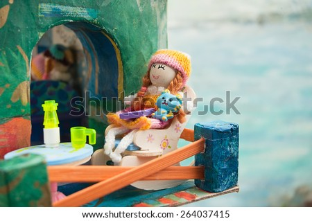 doll on the balcony of toy house, on a background of the sea - stock photo