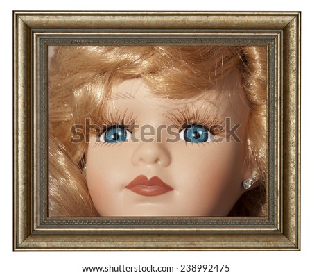 Doll - Portrait of a baby doll in a gold frame - stock photo