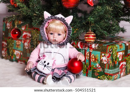 doll under the Christmas tree with gifts