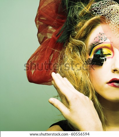 Doll. Young pretty lady with creative make-up and in exotic hat. - stock photo