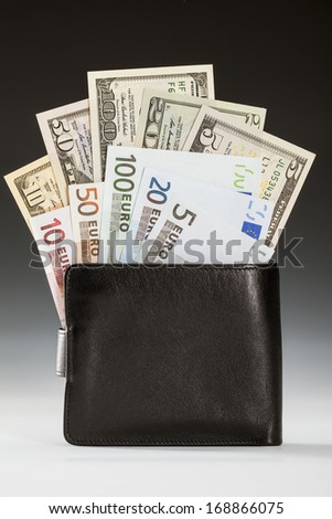 Dollar and euro banknotes in leather wallet on dark background - stock photo