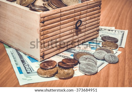 Dollar and euro money with coins in the treasure chest. toned image - stock photo