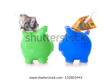 Dollar and euro notes and syringes sticking out of green and blue piggy banks - stock photo