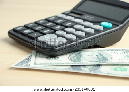 Dollar and some business objects is on the desk. - stock photo