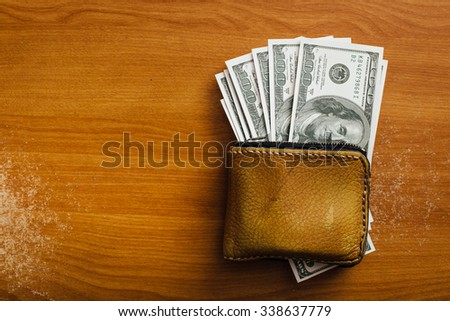 dollar and wallet on wooden table