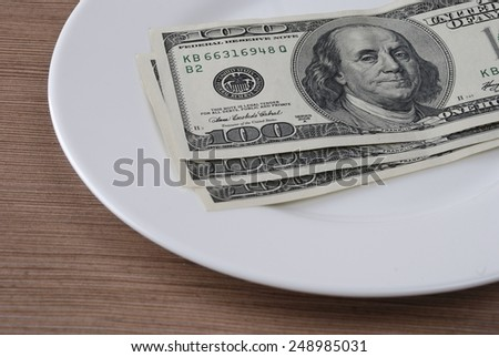 Dollar bank note money in the white plate on the wooden table background  - stock photo