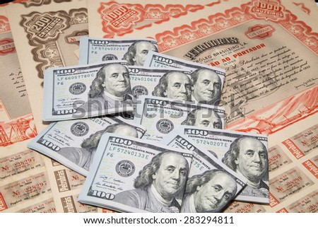 Dollar bank notes over antique bonds