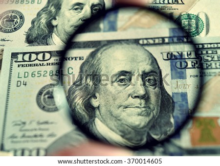 Dollar banknote through magnifying lens (corruption, lobbying, inflation, financial secrecy - concept). Vintage effect. - stock photo