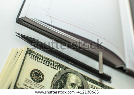 dollar banknotes and the diary with a pencil lying on flat at an angle