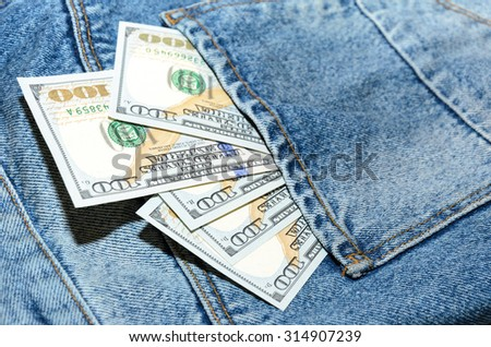 Dollar banknotes in jeans back pocket - stock photo
