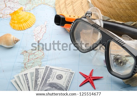 Dollar banknotes on a map with snorkel mask