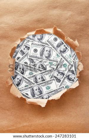 Dollar banknotes through torn craft paper - stock photo